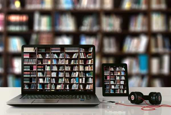 Computer and tablet in front of a bookshelf
