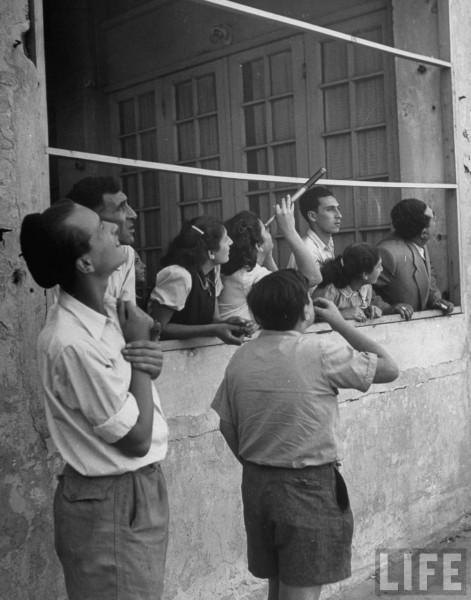 People along the waterfront watching an air raid. May 1948. Frank Scherschel