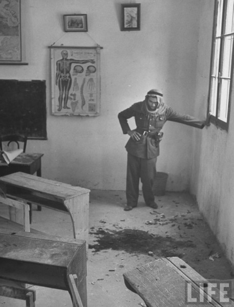 A man looking at blood in an Arab classroom, May 1948. John Phillips