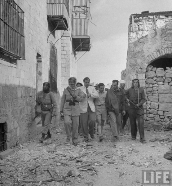Dr. Moussa Husseini (4R), and a leader of Haganah forces, walking with Arab soldiers after signing the surrender of Jerusalem