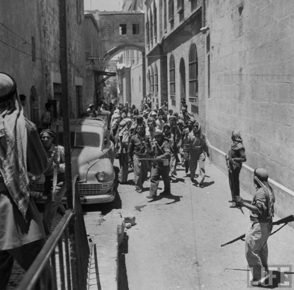 Jewish prisoner being escorted by Arab soldiers
