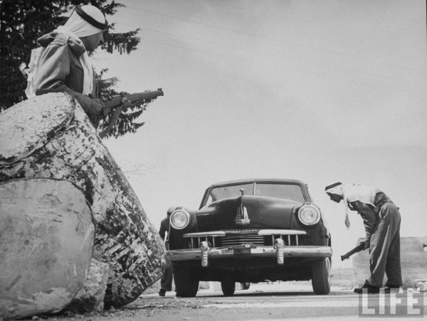 An Arab guard checking a car at the road block