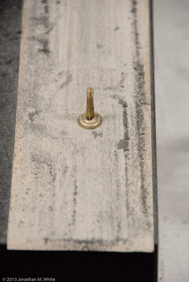 A brass saw nut being cleaned on 320 grit sandpaper.