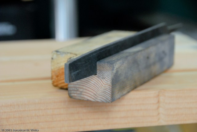 A scrap of wood, kerfed to hold a mill file.