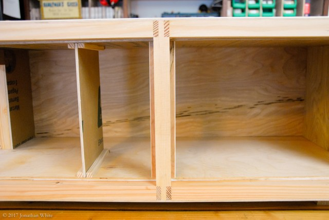 The divider is held in place by some wooden strips that are glued to the inside of the box.