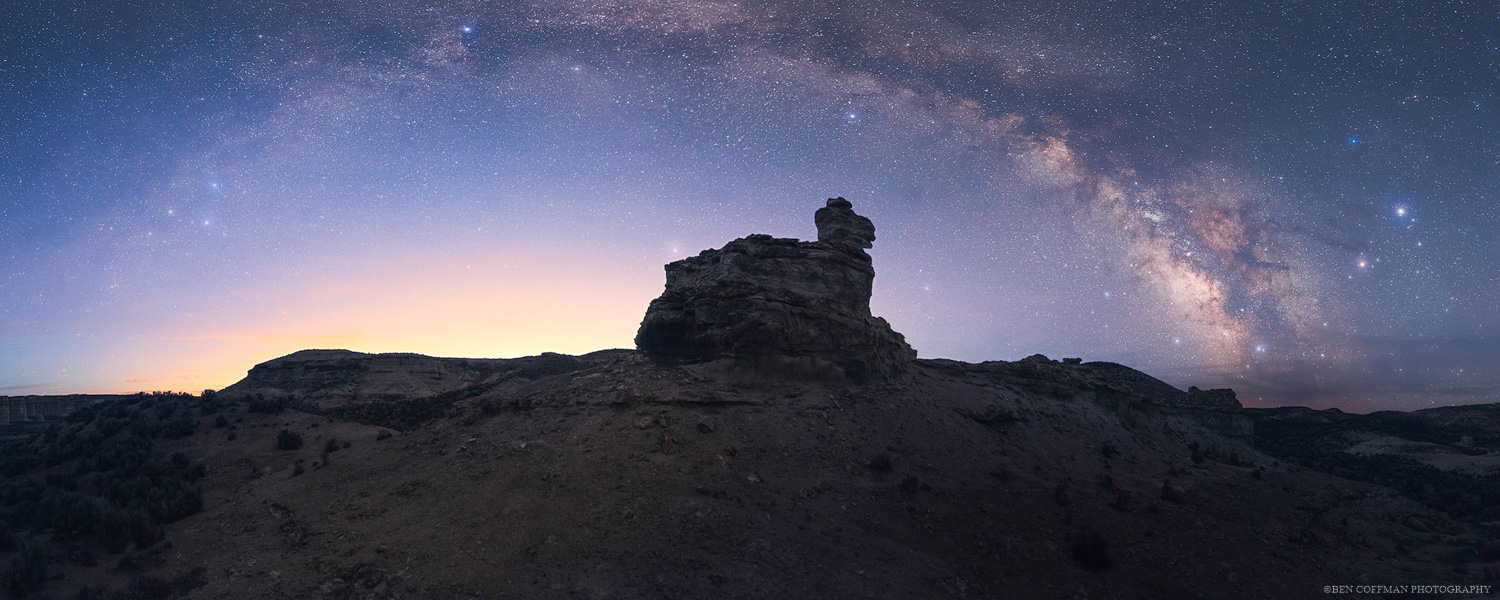 The Milky Way arches over a rock at Pillars of Rome, Oregon.