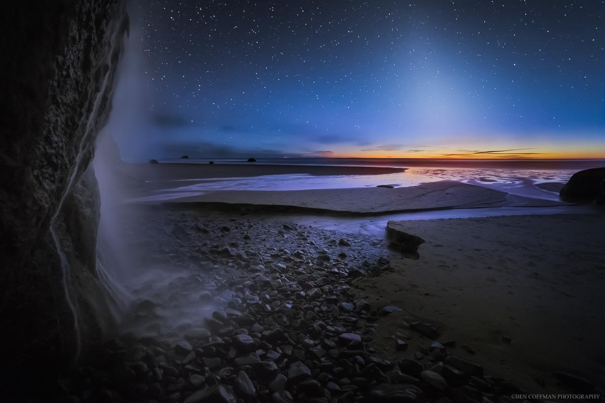 A waterfall flows toward zodiacal light on the Oregon coast.
