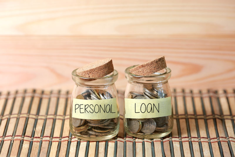 Personal Loan on two jar with wooden pallet background