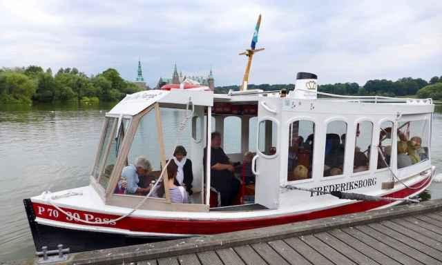 Ein kleine weisses Schiff auf einem See. Die M/S Frederiksborg fährt dich zur Frederiksborg in Hillerød.  Ein tolles Ausflugsziel in Nordseeland