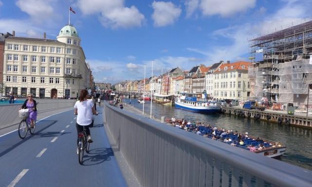 Ein Frau radelt über eine Brücke zum Nyhavn, Kopenhagen