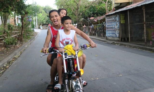 Mann und zwei Kinder auf einem Motorrad in den Philippinen