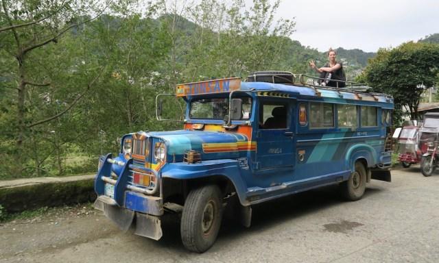 Eine Touristen sitzt auf dem Dach eines blauen Jeepneys und zeigt ein Peacezeichen