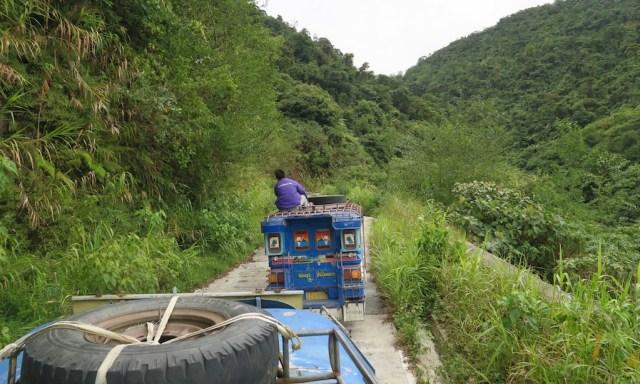 Ein Mann sitzt auf einem Jeepney in der grünen Bergwelt der Philippinen