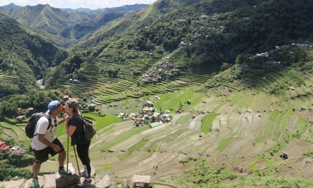 Ein Pärchen küsst sich auf dem Amphitheater von Batad. Im Hintergrund das Tal.