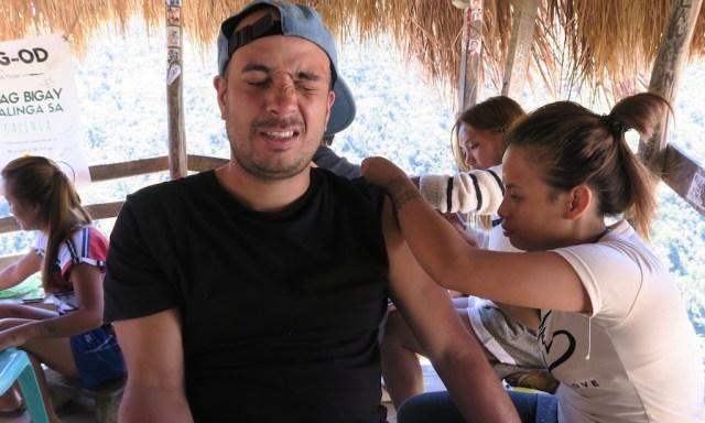 Großnichte von Apo Whang-Od tätowiert einem Reisenden, der ein schmerzverzehrtes Gesicht macht, ein Tattoo auf den Arm