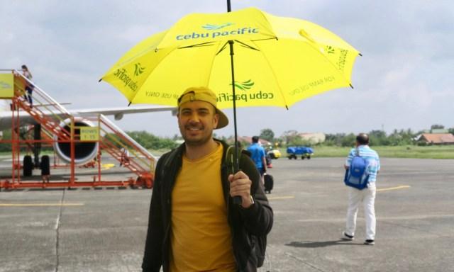 Ein Halbphilippino mit einem gelben Sonnenschirm von Cebu Pacific Airlines auf dem Rollfeld vor einem Flugzeug am Flughafen Cauayan
