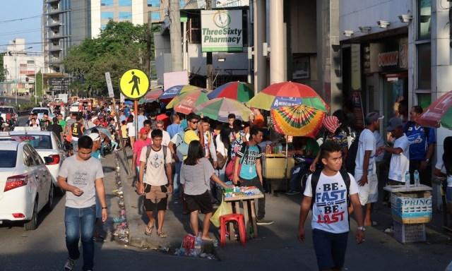 Leute auf einem Bürgersteig in Cebu City. Man sieht Bunte Schirme von Straßenständen