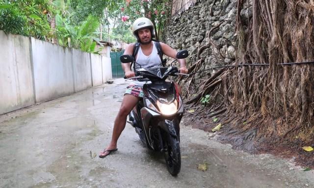 Ein Urlauber mit Helm auf einem schwarzen Scooter in einer Gasse