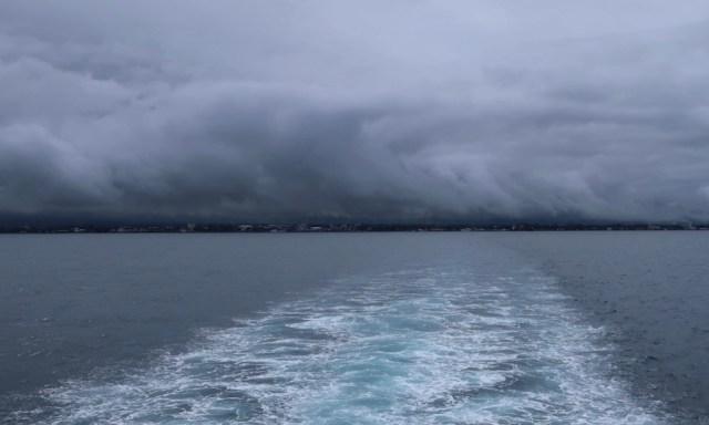 Blick von der Fähre auf das verregnete Negros mit tiefen dunklen Wolken