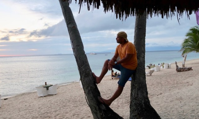 Bendja lehnt zwischen zwei Palmen am Strand des Coco Grove Beach Resorts auf Siquijor