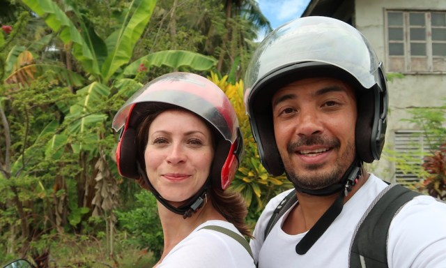 Zwei deutsche Touristen machen ein Selfie auf einem Scooter mit Motorradhelmen auf den Kopf