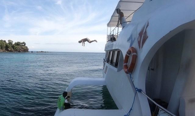 Bendja springt von der Coco Adventurer während sie vor Apo Island liegt