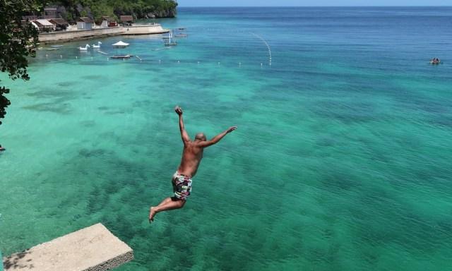 Ein braungebrannter Tourist springt von der Sprungplattform ins türkise Wasser des Salagdoong Beaches