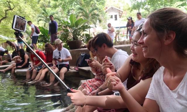 Touristen machen ein Selfie mit einer Selfie Stange am Becken des Balate Trees