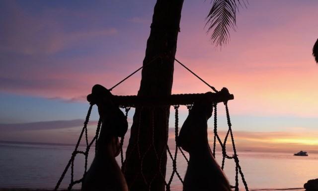 Lila Sonnenuntergangshimmel betrachtet aus einer Hängematte