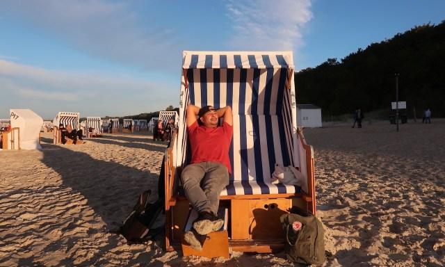 Bendja chillte in einem rot-blau-gestreiften Strandkorb in Kolberg und genießt die Sonne
