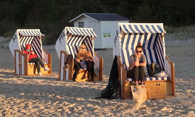3 Strandkörbe in Kolberg wo Leute drin chillen und das sonnige Herbstwetter geniessen