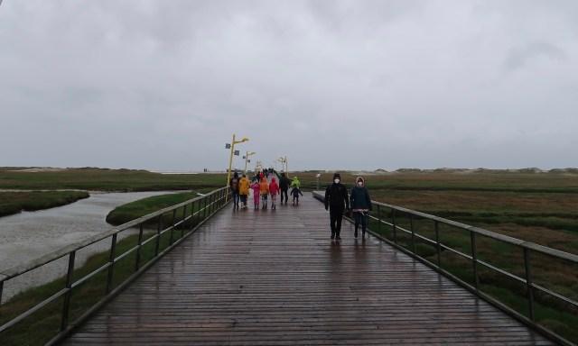 Seebrücke bei schlechtem Wetter. Passanten tragen Corona-Masks
