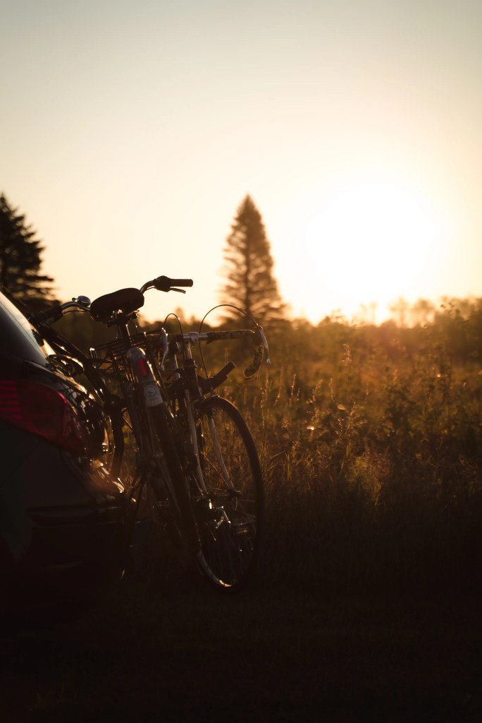 beautiful golden hour photo of Ben's road bike and Natalia's vintage upright bike strapped to the back of her Nissan Versa