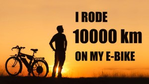 """ben, standing in a gorgeous sunset photo with his ebiek on the left and the words """"I RODE 10000 KM ON MY E-BIKE"""" to the right of him"""