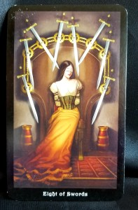 Eight of Swords - A Blindfolded woman standing beneath eight swords, tips pointed at her.