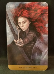 Eight of Wands - Red headed woman holding a bow and arrow, looking directly at her target