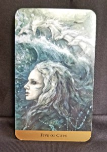 Five of Cups Tarot Card Woman in the waves with white horses running in the spray