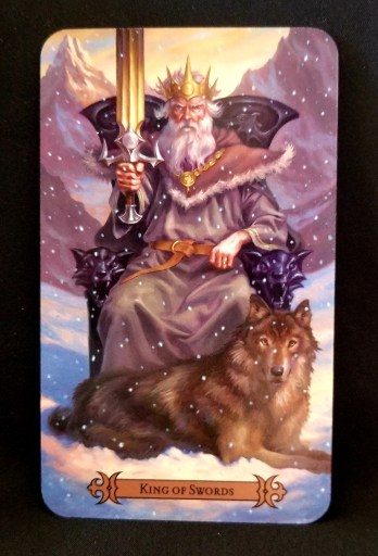 King of Swords - Tarot:n A King dressed in winter robes seated on a throne and holding a sword. A wolf is at his feet