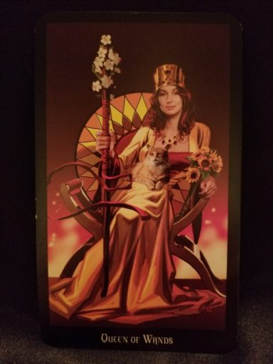 Queen of Wands-Tarot Card: Woman sitting on a throne, a cat in her lap, holding a flowered staff