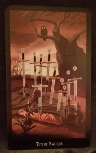 Ten of Swords - a man lying on his stomach with ten swords sticking out of his back