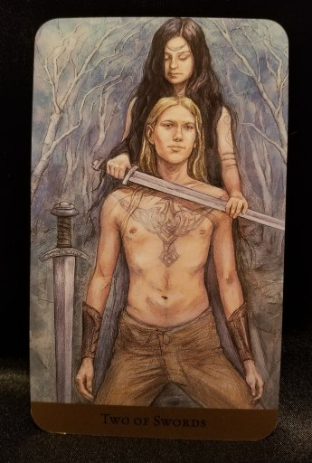 Two of Swords - Tarot Card: a man kneeling while a women stands behind holding a sword to his neck