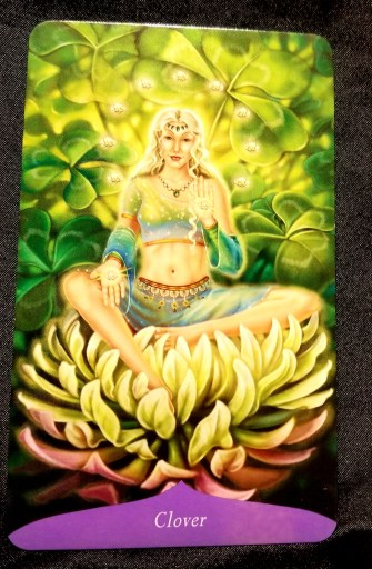 Clover Oracle Card - a woman seated on a  clover blossom