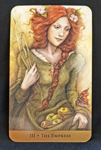 Empress - A beautiful red haired woman holding a basket of apples and a shock of wheat