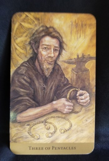Three of Pentacles- a man diligently working on three torques