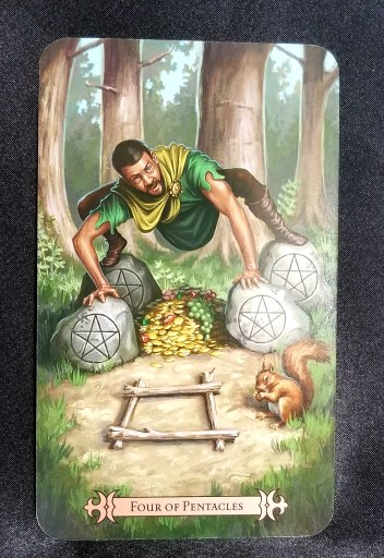Four of Pentacles-Tarot Card:  A man balancing with arms and legs on four pentacle stones.  Beneath him is a full horn of plenty.
