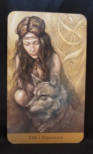 Strength Tarot Card - Woman crouched next to a wolf