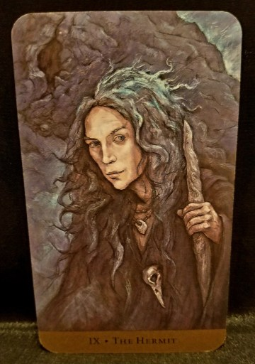 The Hermit Tarot - An older woman with grey hair, dressed in black. with a ravens skull around her neck clutching a heavy staff