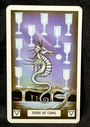 Nine of Cups - Tarot Card: A seahorse dragon hovering over the sea, surrounded by nine silver chalices