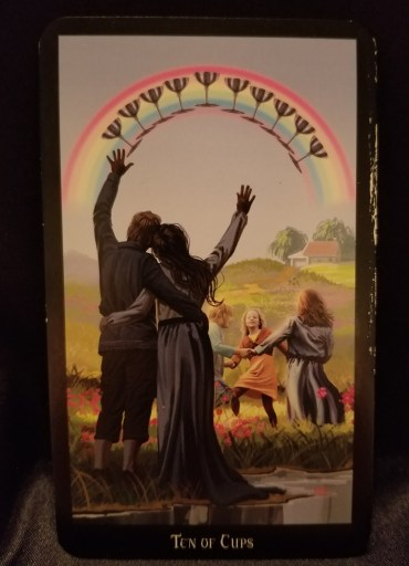 Ten of Cups - Tarot Card:  A man and a women, their arms about each other, looking on as children dance in a meadow.  A rainbow with 10 cups is overhead.