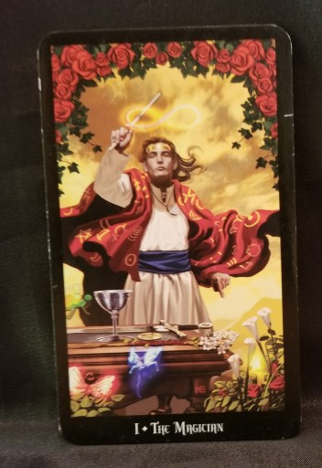 The Magician - Tarot Card - a Magician standing in front of an altar waving a wand.